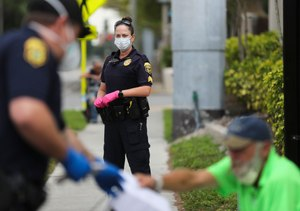 Clearwater Police officer Joseph Czop, on left, and Sgt. Meg Hasty, in center, both wearing protective face masks and gloves. Law enforcement officers are facing a new array of challenges policing during a global pandemic. Image: Dirk Shadd/Times via TNS