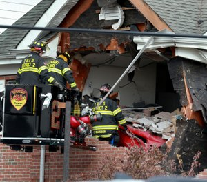 Firefighters inspect a car that crashed into the second story of a building in New Jersey Sunday morning. (Photo/Ed Murray, NJ Advance Media)