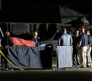Investigators move the body of a man who is reportedly Michael Forest Reinoehl after he was shot and killed by law enforcement on September 3, 2020 in Lacey, Washington. (Nathan Howard/Getty Images/TNS)