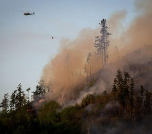 A helicopter heads back to a water source to get more water to dump on the Dowens Road 2 Fire near the Dorena Grange near Cottage Grove.  (Photo/Andy Nelson, The Register-Guard, Tribune News Service)