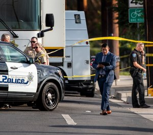 San Bernardino, California, homicide detectives investigate the scene where two San Bernardino Police Officers were wounded in a shootout with a suspect who was allegedly involved in shooting a San Bernardino County Sheriff Deputy the day before, on Wednesday, Aug. 18, 2021, in Highland, California. The suspect died at the scene.