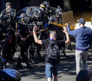 Seattle Police use pepper spray on protesters as they advance their line during a