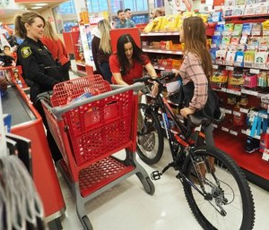 San Joaquin County sheriff's Detective Teresa Morgan, left, watches as Natalie wheels her new bike through checkout during Wednesday's fourth annual Blue Santa event. (Calixtro Romias/The Record via Tribune News Service)