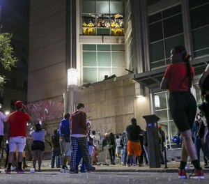 During a security breach earlier this year, onlookers watch from the street as inmates chant and throw things from broken windows at the St. Louis Justice Center.