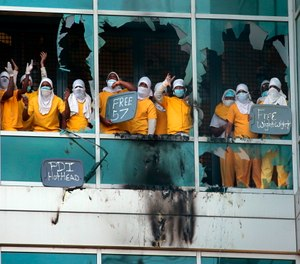 Inmates yell from broken windows at the St. Louis Justice Center, known as the city jail, after fires were set at the facility on Feb. 6.