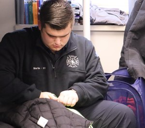 Brendan Martin sits on his bed Friday, Feb. 7, 2020, in his dorm room at the Maynard Firehouse in Marcy. He shares the dorm with two other SUNY Polytechnic Institute students; the students volunteer with the fire department in exchange for housing.