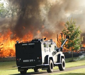 A SWAT team was called to the scene of a Minnesota house fire where an armed individual has barricaded themselves in a trailer near where firefighters were battling the blaze.