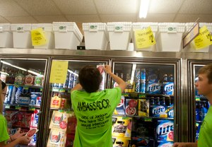 A teen puts a sticker on a beer cooler as part of a project to raise awareness of underage drinking. Image: Sam Gause/MLive Media Group
