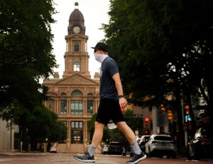 Wearing a mask, Matthew Lubinski of Bedford walks through downtown Fort Worth past the old Tarrant County Courthouse, Thursday, July 2, 2020. As cases of the coronavirus surge to record highs, Gov. Greg Abbott on Thursday ordered Texans to wear face masks in public in counties with outbreaks of COVID-19. Image: Tom Fox/Dallas Morning News via TNS