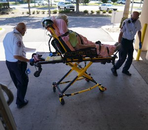 Tom Canady, 76, and Kent Marchuk, 67, with the Sun City Center Emergency Squad, wheel an 86-year-old, male patient into the emergency room after picking him up for dizziness, on Monday, May 4, 2020 in Sun City Center. (Photo/Martha Asencio Rhine, Tampa Bay Times)