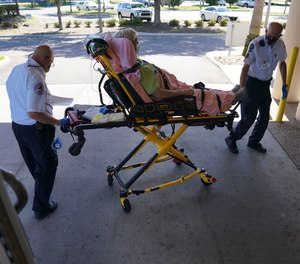 Tom Canady, 76, and Kent Marchuk, 67, with the Sun City Center Emergency Squad, wheel an 86-year-old, male patient into the emergency room after picking him up for dizziness, on Monday, May 4, 2020 in Sun City Center.