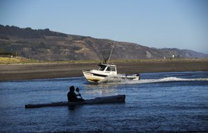 A kayaker paddles out as a fisherman returns in Bolinas Bay. Image: Gina Ferazzi via TNS