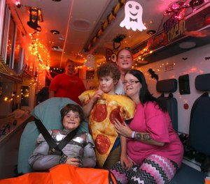 Amanda Mulls (in pink) poses with her children, Evan Stafford, 11, Colton Stafford, 11, and Willow Mull, 14, in the back of a GEMS ambulance prior to going trick-or -treat in the Riverwood Plantaion neighborhood Halloween evening. [Mike Hensdill/The Gaston Gazette]