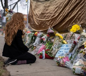 A mourner visits the location where a gunman opened fire at King Soopers grocery store on Monday on March 23, 2021, in Boulder, Colorado. Ten people were killed in the attack.