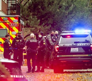Police officers from different local jurisdictions investigate the scene where two King County Sheriff's deputies were injured in a gunfight with an armed man in Woodinville, Washington on Monday afternoon, Nov. 9, 2020.