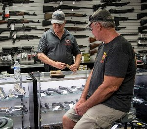 Mike Fiorille, business partner at Get Loaded, serves a customer at the gun store on June 30, 2016, in Grand Terrace, Calif.