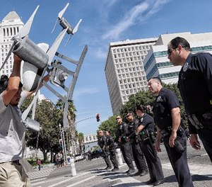 Miguel Guzman flaunts a drone replica in front of Los Angeles Police Department officers after a group blocked downtown traffic, protesting the the LA Police Commission vote to allow the LAPD to use drones, on Tuesday, Oct. 17, 2017.