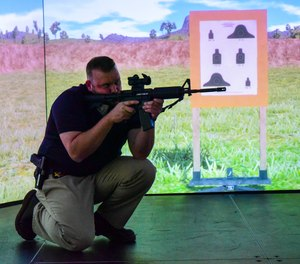 The Utah Attorney General's Office provides a training center for law enforcement throughout the state. Here, Special Agent Chris Walden hones his marksmanship skills on their VirTra simulated long gun range. (image/Utah AG Training Center)