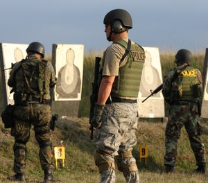 A SWAT firearms instructor and two students on the firing range.
