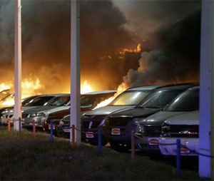 Cars burn at a dealership Tuesday, Nov. 25, 2014, in Dellwood, Mo. A grand jury has decided not to indict Ferguson police officer Darren Wilson in the death of Michael Brown, the unarmed, black 18-year-old whose fatal shooting sparked sometimes violent protests. (AP Photo/Charlie Riedel)