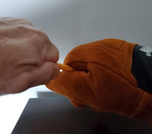 To text dexterity, theauthor tries to pull a pencil out of the grip of the Victory Structural Fire Glove, without success.