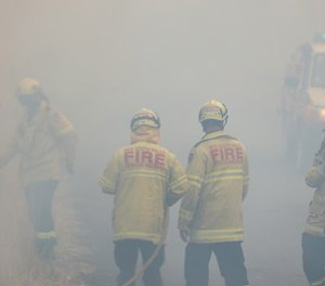 Firefighters take a break in smoke while battling bushfires near Taree, New South Wales, Australia on Monday, Nov. 11, 2019. A devastating start to the Australian bushfire season has prompted a state of emergency in the eastern state of New South Wales, with the country's largest city, Sydney, bracing for