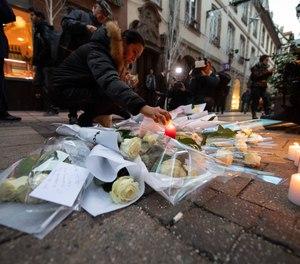 A woman lights a candle near the Strasbourg Christmas market. (Photo/Sebastian Gollnow/DPA/ABACAPRESS.COM)