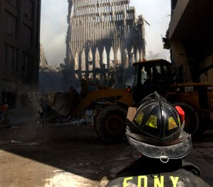 An FDNY firefighter looks up at what remains of the World Trade Center after its collapse during the Sept. 11 terrorist attack. (Photo/U.S. Navy Photo by Photographer's Mate 2nd Class Jim Watson)