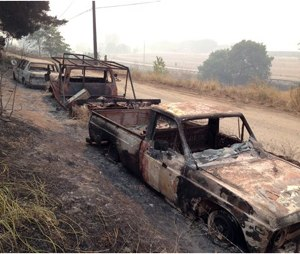 Burned cars sit along US Route 97, in Pateros, Wash., Friday. Authorities say the wildfire has already burned about 100 homes and prompted the evacuation of Pateros, home to about 650 people in Okanogan County. A hospital in nearby Brewster was also evacuated as a precaution. (AP Photo/The Seattle Times, Mike Siegel)