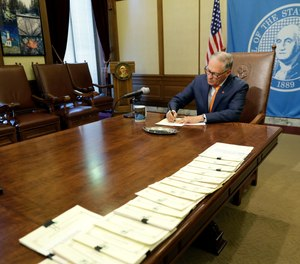 Washington Gov. Jay Inslee makes notes during a quiet moment during a bill signing ceremony, Tuesday, May 7, 2019, at the Capitol in Olympia, Wash.