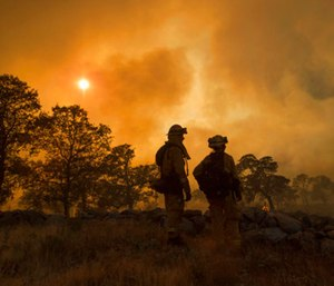 The fast-moving wildfire in the Sierra Nevada foothills destroyed structures, including homes, and led to several minor injuries, fire officials said Saturday as blazes threatened homes around California during a heat wave. (AP Photo/Noah Berger)