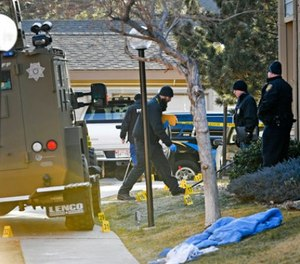 Authorities investigate the shooting of several sheriff's deputies in an apartment complex in Denver on Sunday, Dec. 31, 2017.