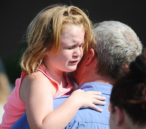 Lilly Chapman, 8, cries after being reunited with her father, John Chapman at Oakdale Baptist Church on Wednesday, Sept. 28, 2016, in Townville, S.C. Students were evacuated to the church following a shooting at Townville Elementary School.