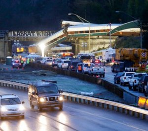 Traffic moves along northbound Interstate 5, left, as southbound lanes are filled with emergency vehicles near the scene of an Amtrak train crash Monday, Dec. 18, 2017, in DuPont, Wash.