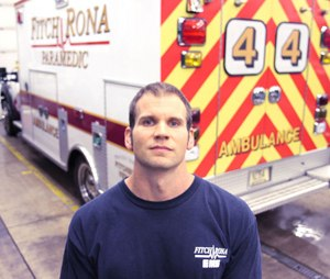 """Paramedic Ross Williams is photographed in the Fitchburg Fire Department garage. Williams is the one who gained Andrew's trust and carried him down the stairs at the Oneida Street house seven years ago. Andrew, which is no longer his name, remembers Williams. """"That's an honor,"""" Williams said."""