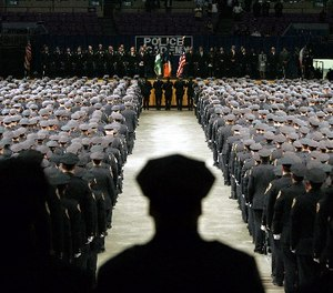 In this file photo of July 13, 2005, New York City Police Academy graduates stand at attention during the presentation of colors at Madison Square Garden in New York.