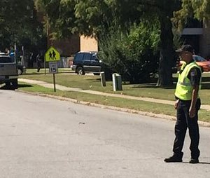 A law enforcement officer stands watch as emergency vehicles clog a road adjacent to Delta State University after an active shooter was reported in Cleveland, Miss., Monday, Sept. 14, 2015.