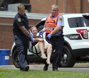 Emergency personnel carrying a volunteer with simulated injuries is carried during a training exercise for an active shooter at Hopewell Elementary School, Wednesday, May 25, 2016, in West Chester, Ohio.