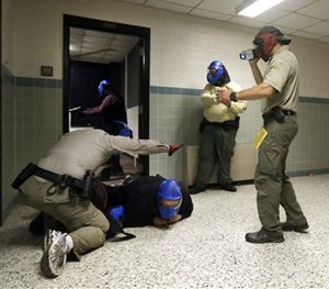 In this Aug. 13, 2013 photo, FBI instructor Mike Sotka, center, films local officers as they participate in an active shooter drill in a college classroom building in Salisbury, Md.