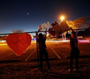 A student at Marjory Stoneman Douglas High School hangs signs on the fence of the school.