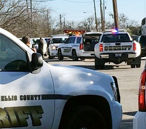 Law enforcement personnel from the Ellis County Sheriff's Office park outside a high school in Italy, Texas, following an active shooter incident at the school Monday morning, Jan. 22, 2018.