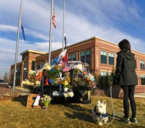 With flags at half staff, Maribeth Forst, with her dog Max, stands near a makeshift memorial on a police cruiser for the victims of what authorities describe as an ambush Monday, Jan. 1, 2018, at the Douglas Country Sheriff Substation in Highlands Ranch, Colo.