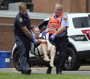 Emergency personnel carry a volunteer with simulated injuries during a training exercise for an active shooter, Wednesday, May 25, 2016, in West Chester, Ohio.