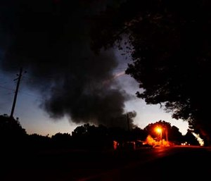 Light from a light pole shows a house near a plume of smoke from a Colonial Pipeline explosion.