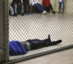 In this Thursday, June 26, 2014, photo a man lays on the floor of a holding cell at the Cook County Jail before his initial bond hearing in Chicago. (AP Photo/Charles Rex Arbogast)