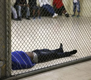 In this Thursday, June 26, 2014, photo a man lays on the floor of a holding cell at the Cook County Jail before his initial bond hearing in Chicago.