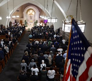 Mourners stand during the funeral Mass for Detective Luis Alvarez, at Immaculate Conception Church, in the Queens borough of New York, Wednesday, July 3, 2019. (AP Photo/Richard Drew, Pool)