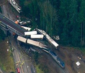 The train derailed about 40 miles (64 kilometers) south of Seattle before 8 a.m., spilling at least one train car on to busy Interstate 5. (KOMO-TV via AP)