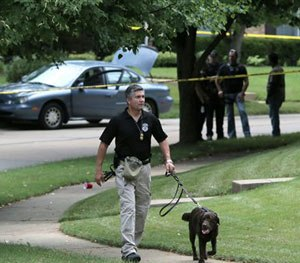 Police secure the scene and a suspect's vehicle in Ballwin, Mo., Friday, July 8, 2016, after a Ballwin police officer was shot during a confrontation with a man on a street. (AP Image)