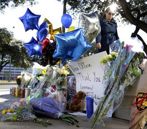 A woman leaves flowers at a make-shift memorial for slain San Antonio police officer Benjamin Marconi, 50, a 20-year veteran of the force, Monday, Nov. 21, 2016, in San Antonio.